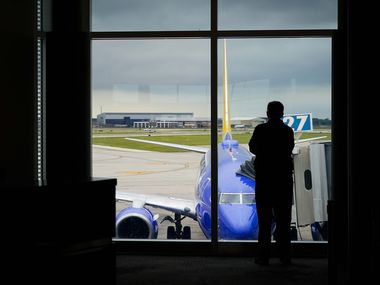 A man looks out over a Southwest Airlines 737 parked at a gate at Houston Hobby Airport on Friday, March 20, 2020, in Houston.