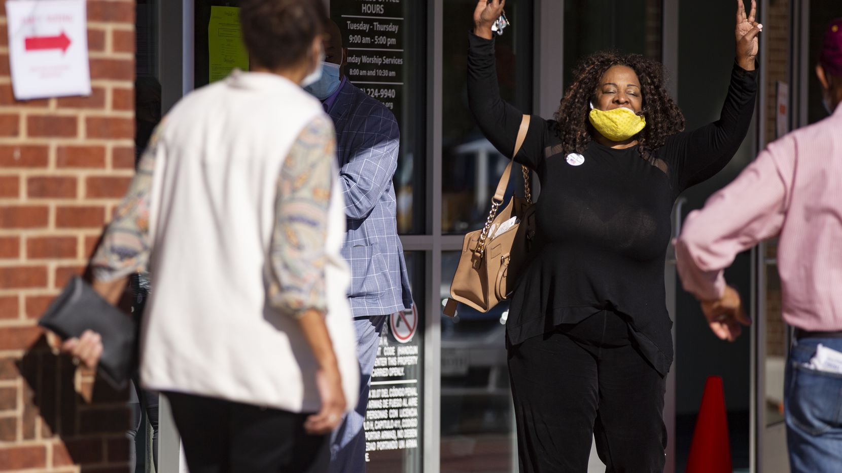 """Jacqueline Johnson celebrates after voting at Disciple Central Community Church in DeSoto on Oct. 13, 2020. Johnson waited two and a half hours to vote. """"We all ought to be out here,"""" Johnson said. """"I'm retired but I'm determined."""""""