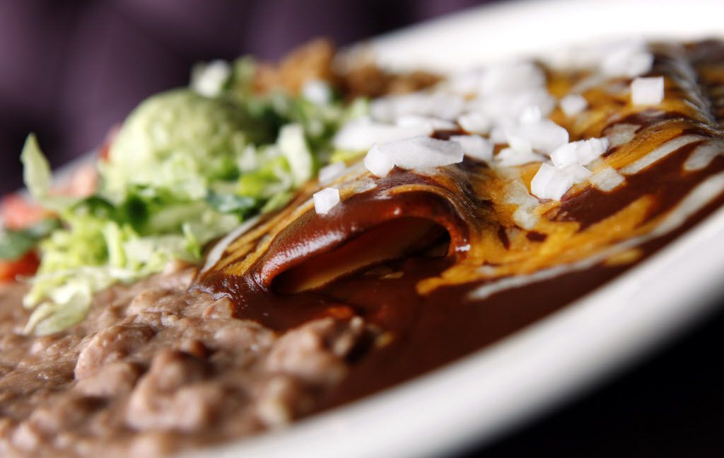 """Tex-Mex cheese enchiladas: To be authentic, they must be filled with processed cheese or yellow cheddar (chopped onions are optional) and smothered with a traditional, meatless, ground-chile-style """"chili"""" gravy."""