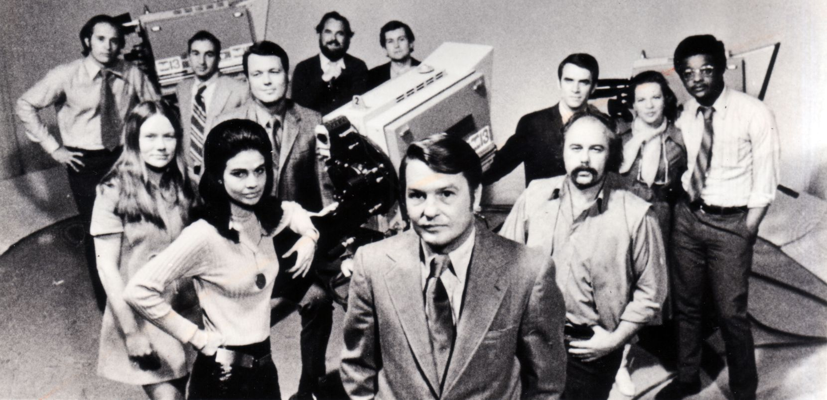 """KERA's award-winning news program """"Newsroom"""" debuted on Feb. 16, 1970, with Jim Lehrer (center) as its editor. Other reporters on the controversial program included Lee Cullum Clark (arm on camera); Bill Porterfield (behind Lehrer); Pat Reed and John Tackett (behind Clark); Darwin Payne, Patsy Swank and Greg Roberson (from left behind Porterfield); and Mike Ritchey, Harlan Cohen, Ron Devillier and Max Woodfin (from left at rear)."""