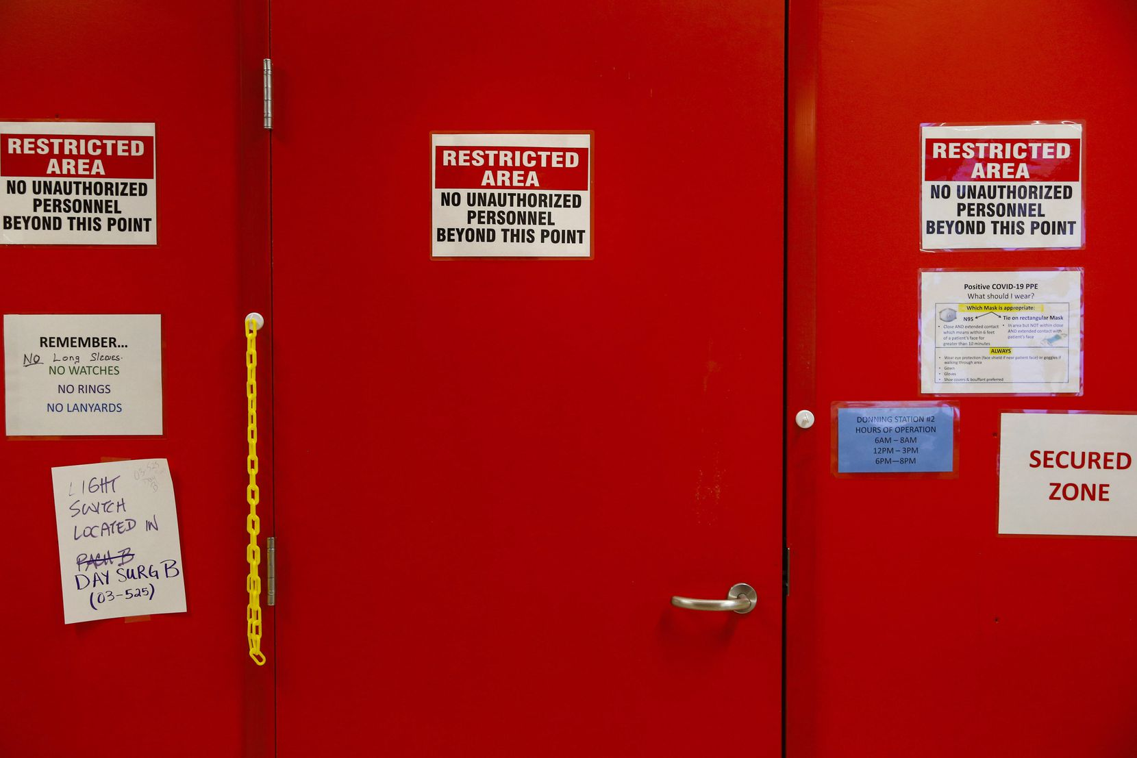 Just on the other side of this door, painted red as a warning of the highly contagious COVID-19 cases on the other side, health care workers don personal protective equipment and then begin their work with patients.