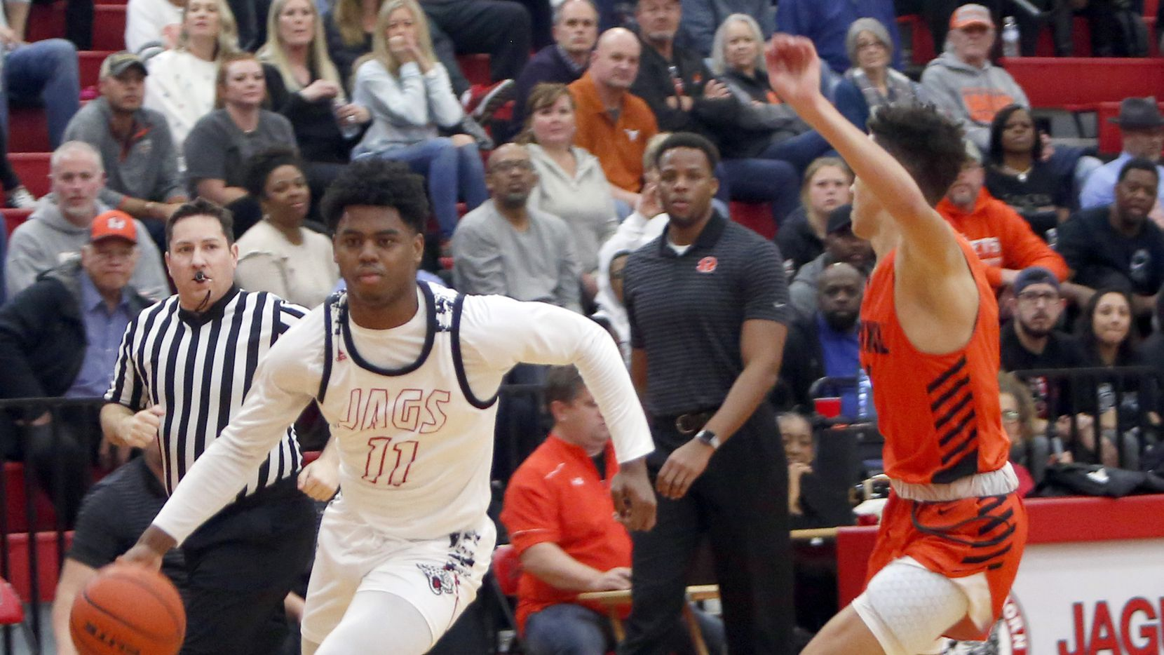 Mesquite Horn's Zaakir Saywer (left) drives to the basket as Rockwall's Logan Hutton defends. Horn won 55-43 to win the District 11-6A title.