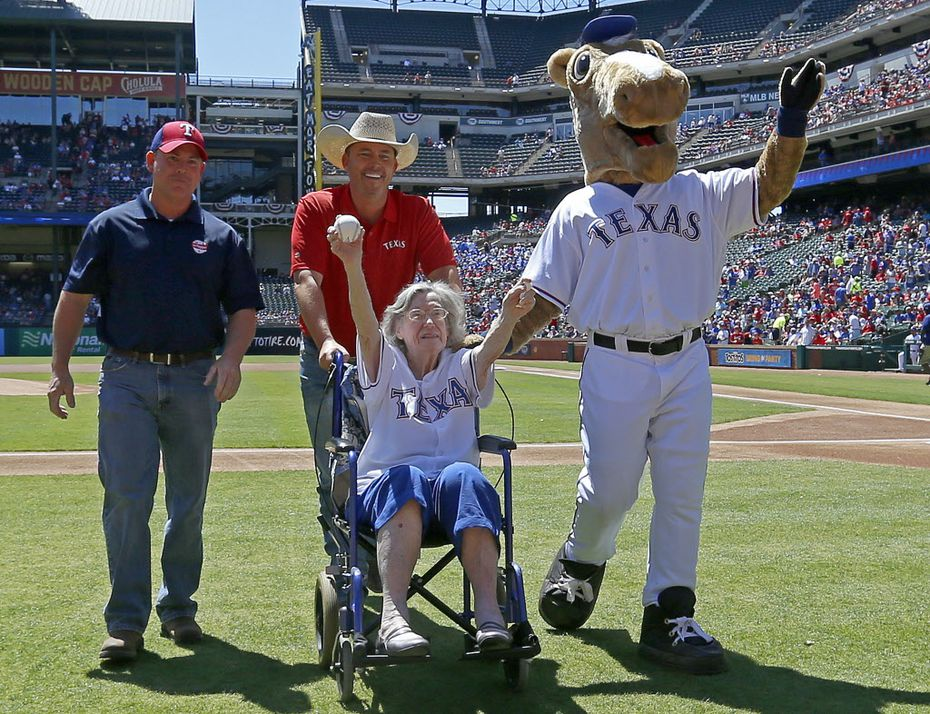 Elizabeth Sullivan, 105-years-old from Fort Worth, on a wheelchair, waves to the crowd as she wheels off with Kirk Conger, of Dr. Pepper, left, Chad Prather, center, and Rangers Captain after she throws out the ceremonial first pitch at the Rangers and Mariners game at Globe Life Park in Arlington, Texas, Wednesday, April 6, 2016. (Jae S. Lee/The Dallas Morning News)