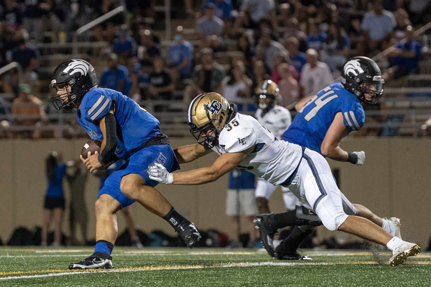 Plano West junior quarterback Vance Feuerbacher (19) tries to escape the tackle of Little Elm senior linebacker Tyson Bope (35) on a scramble during the first half of a high school football game on Friday, Sept. 10, 2021 at John Clark Stadium in Plano, Texas. (Jeffrey McWhorter/Special Contributor)