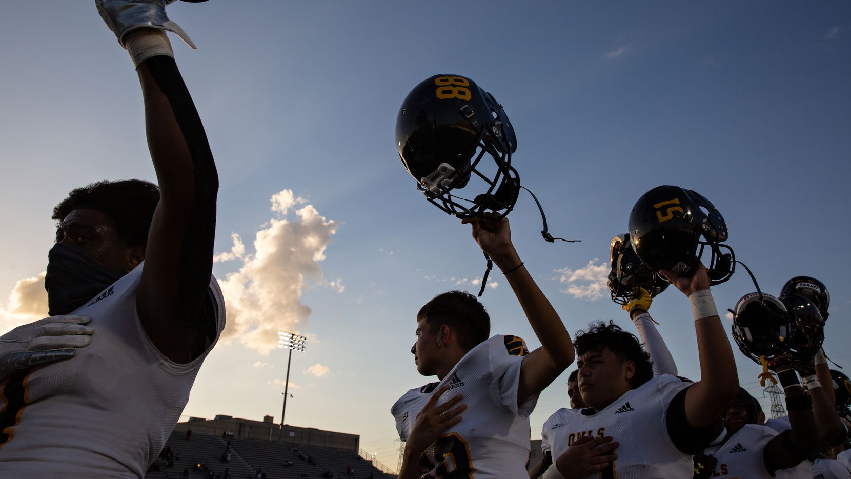 Garland High School football players put their helmets in the air during the Star-Spangled Banner before the season-opening game at Sprague Stadium against Justin F. Kimball High School on August 27, 2021.