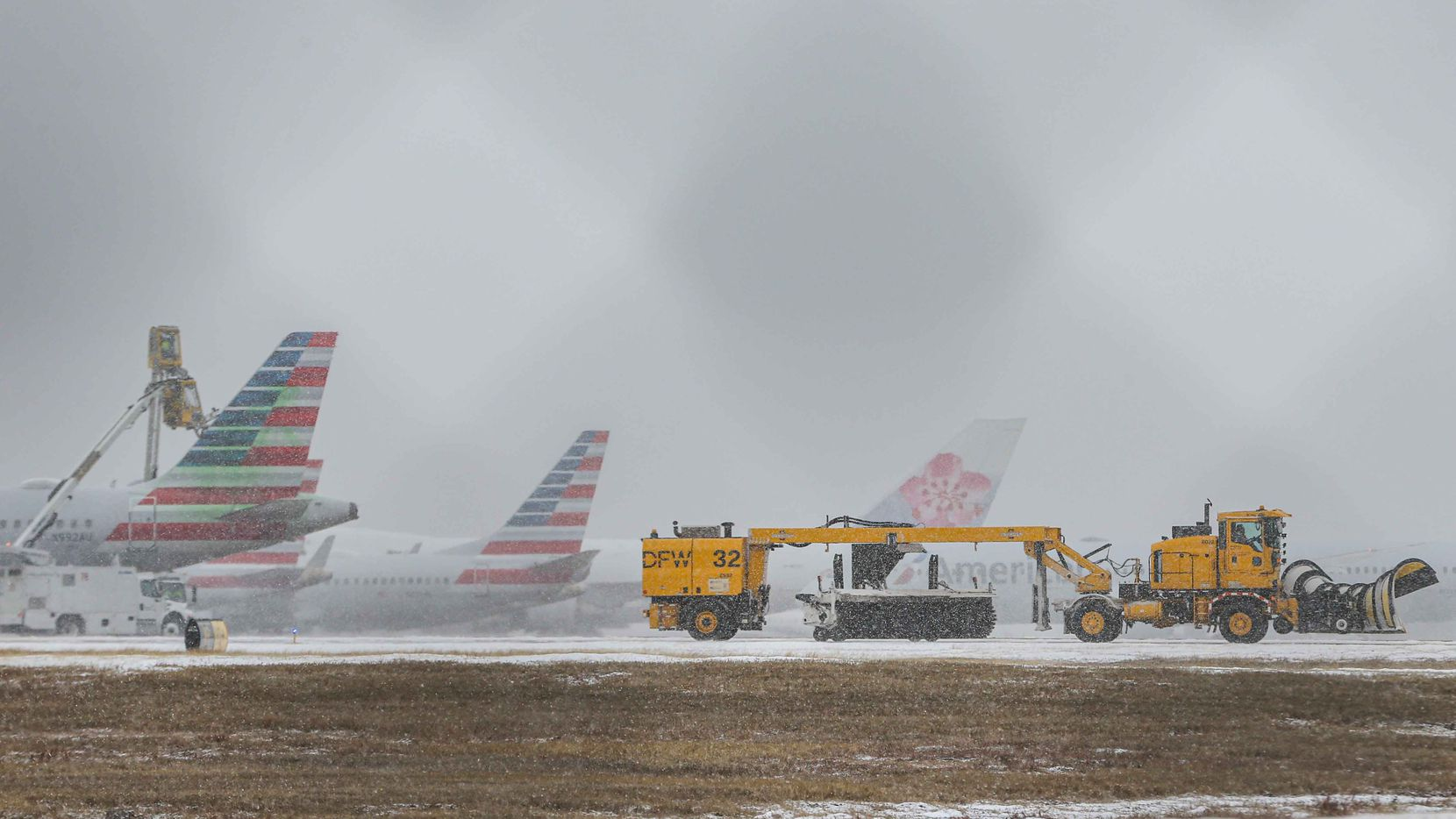 An American Airlines jets get inline to be de-iced at DFW International Airport before takeoff as winter flurries arrive in Irving on Sunday, February 14, 2021 ahead of major snowstorm. (Lola Gomez/The Dallas Morning News)