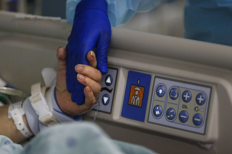 A 73-year-old woman holds a nurse's hand while coming off sedatives before the removal of her breathing tube.
