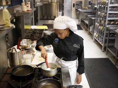 High school junior culinary student Taylor Givens stirs rice pilaf on the stove as she prepares a meal at the Ben Barber Innovation Academy in Mansfield.