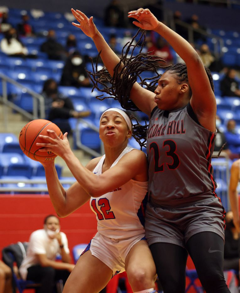 Duncanville's Zaria Rufus (12) is bumped by Cedar Hill's Theasia Ebron (23) as she attempts a shot during the first half of play at Sandra Meadows Arena at Duncanville High School on Tuesday, January 12, 2021 in Dallas. (Vernon Bryant/The Dallas Morning News)
