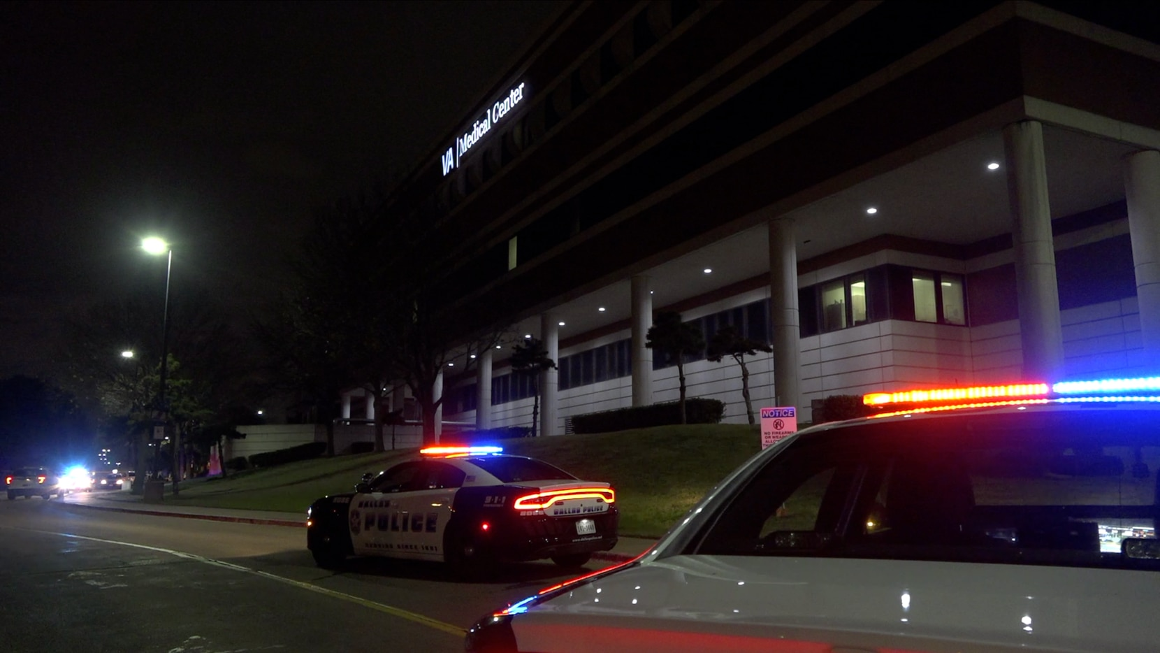 Dallas police squad cars park outside the Dallas Veterans Affairs Medical Center near where a man was fatally shot by hospital police Wednesday night.