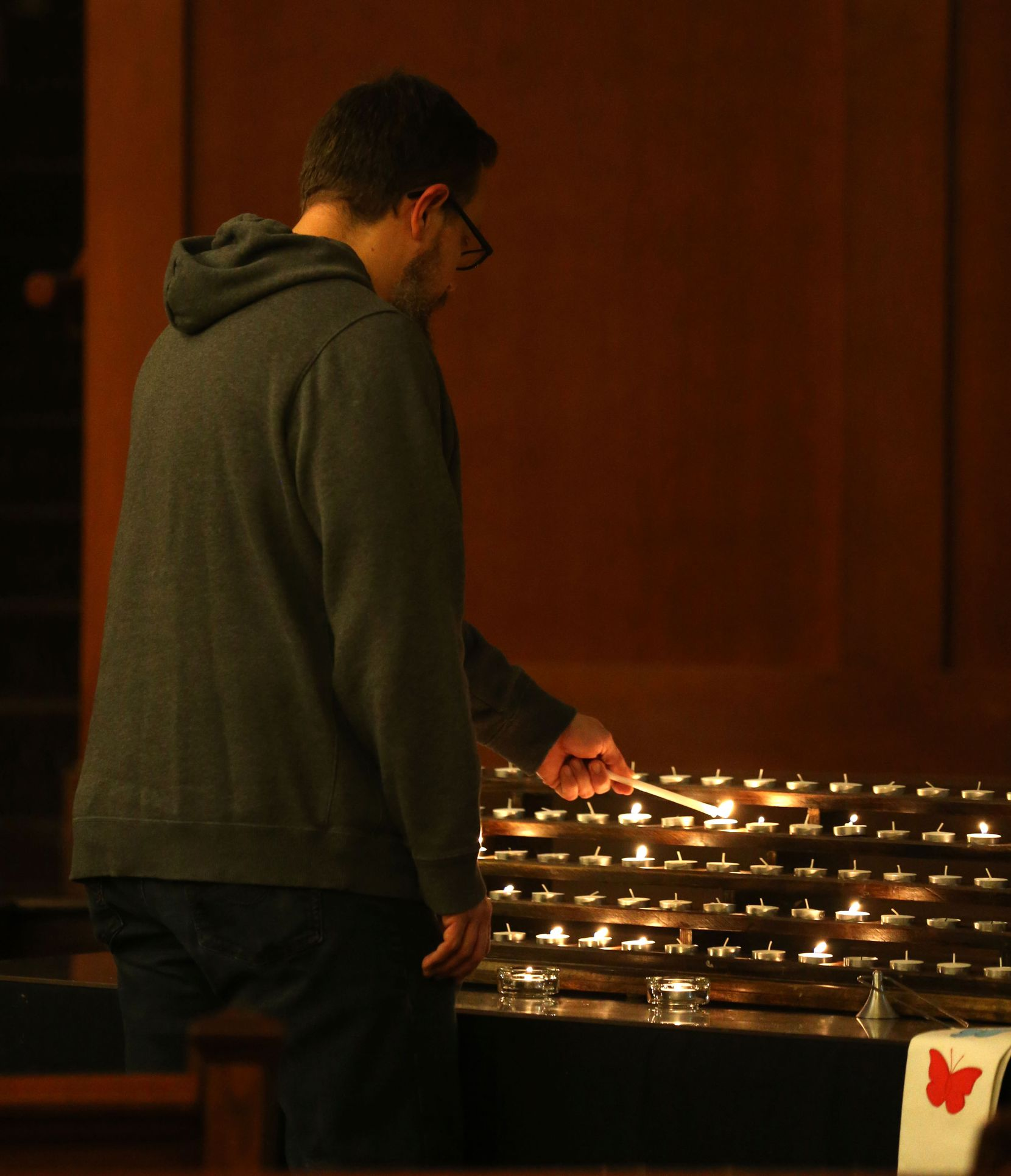 Church member J.J. Heid lights a candle in the sanctuary at Grace Avenue United Methodist Church in Frisco on Wednesday during a prayer service set up after the denomination's anti-LGBTQ vote in St. Louis.