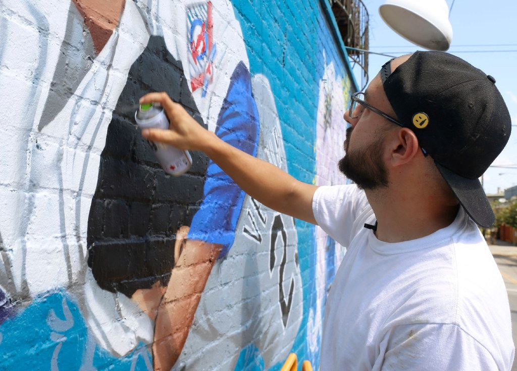 """Dallas-based muralist Isaac """"IZK"""" Davies starts to add detail to the mural of the famous Nolan Ryan punch image on the Crowdus Street side of Wits End in Deep Ellum. The mural was commissioned to promote DJ Edgar Blue No Request Served Sunday's roof top party at Wits End. (Ron Baselice/The Dallas Morning News)"""
