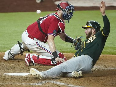Oakland Athletics left fielder Robbie Grossman scores as the throw gets away from Texas Rangers catcher Sam Huff during the ninth inning at Globe Life Field on Friday, Sept. 11, 2020.