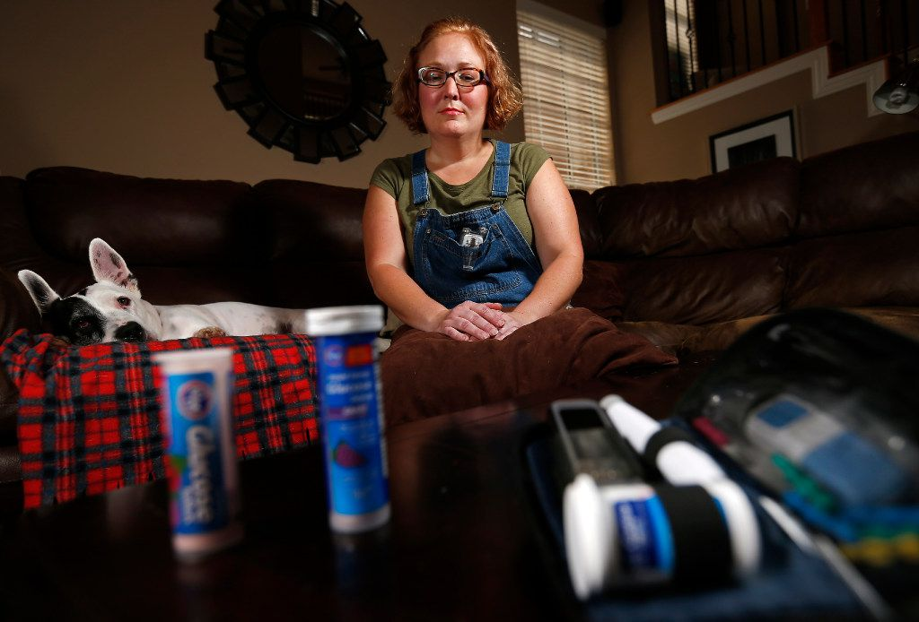 Kelli Bennett, a dog walker, poses for a photograph with her glucose tablets and insulins at her client's home on Wednesday, March 22, 2017, in Flower Mound. Simmy, the client's dog, sits on the couch next to her. Bennett has type-1 diabetes and now is on a plan that costs about $240 a month after a subsidy, and she was able to get a type of insulin pump with a sensor that keeps her blood sugar under control.