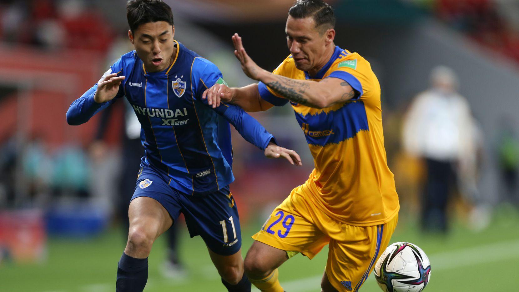El jugador del Ulsan Hyundai, Lee Dongjun (izq), pelea el balón con el mediocampista de Tigres, Jesús Dueñas, en el partido del Mundial de Clubes efectuado en Qatar, el 4 de febrero de 2021.