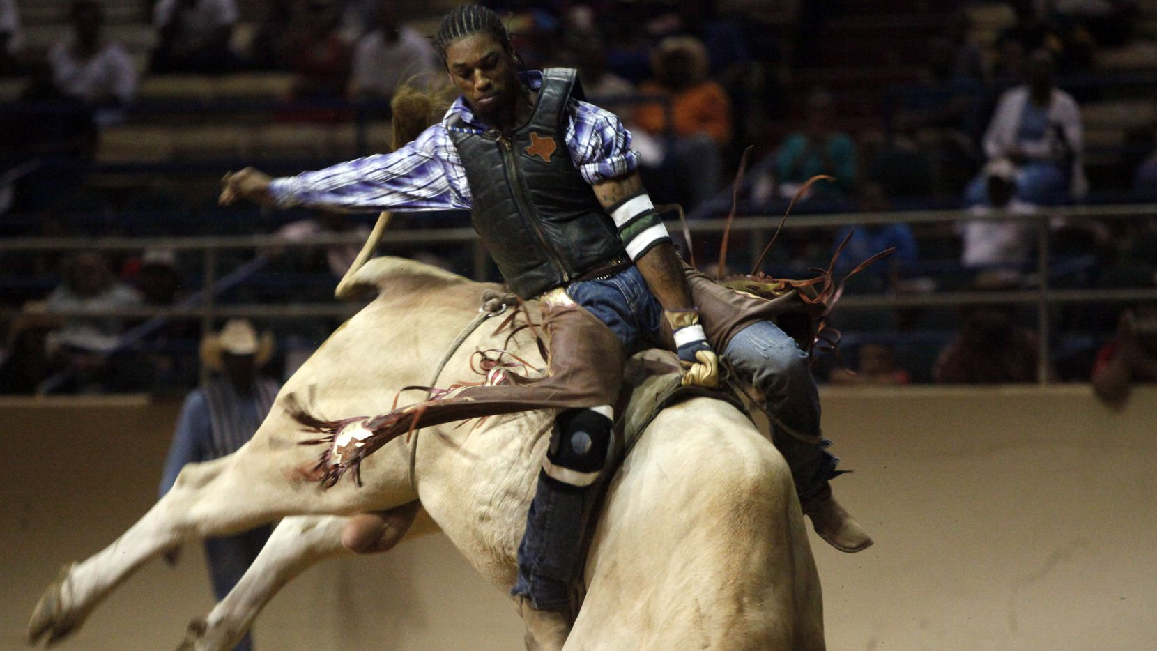 Bull rider Kendrick Mack competes in the bull riding competition at the 26th Annual Texas Black Invitational Rodeo, on Saturday, June 21, 2014 at the State Fair Coliseum in Dallas. The annual rodeo hosted a variety of events and competitions including live music by the Big Charles Young band; bronc riding, steer wrestling, bull riding and a mexican style rodeo performance.