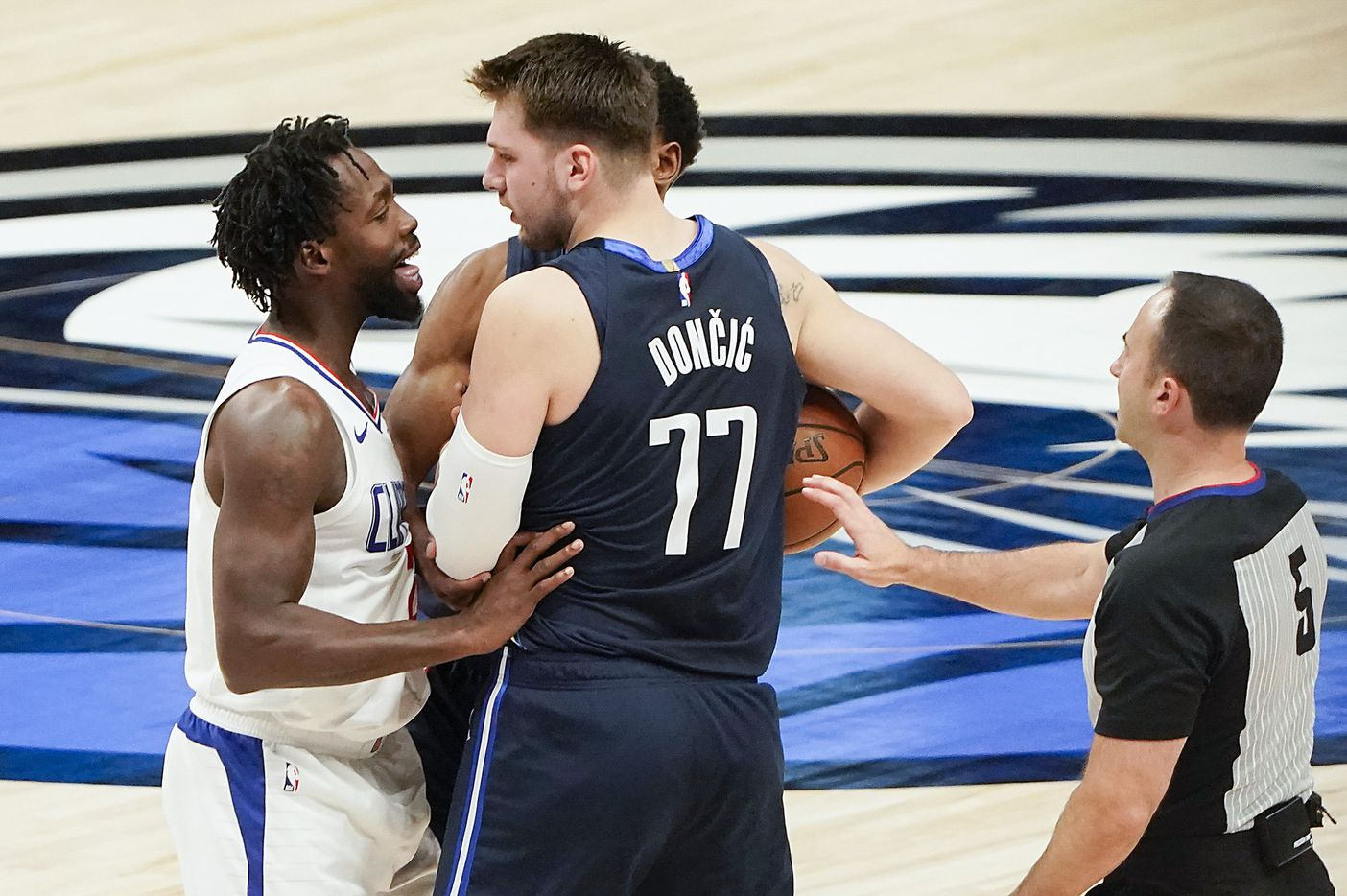 Officials and teammates rush in to separate Dallas Mavericks guard Luka Doncic (77) from LA Clippers guard Patrick Beverley (21) during the first quarter of an NBA playoff basketball game at American Airlines Center on Friday, May 28, 2021, in Dallas.