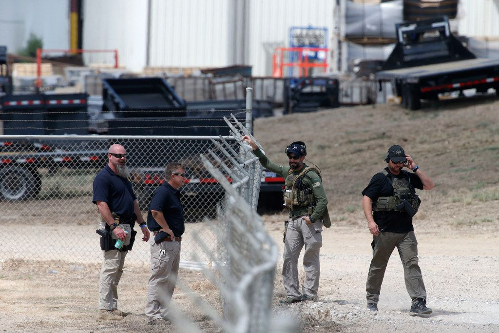Agents from Immigration and Customs Enforcement and other departments meet across the fence at Load Trail LLC. after it raided in Sumner, Texas on Aug. 28, 2018.