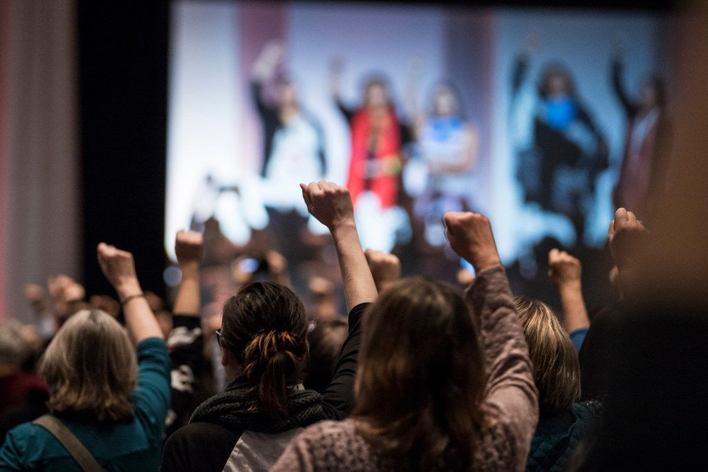 Attendees raise their fists as they hear the opening prayers song offered by five indigenous women during the Women's Convention at Cobo Center in downtown Detroit, Oct. 27, 2017. (Junfu Han/Detroit Free Press)
