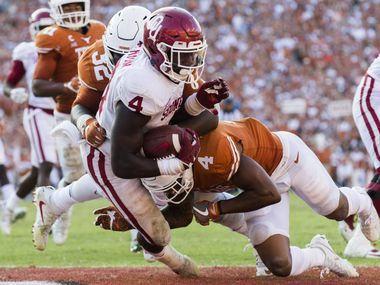 Texas Longhorns defensive end Malcolm Roach (32) and defensive back DeShon Elliott (4) tackle Oklahoma Sooners running back Trey Sermon (4) in the end zone during the fourth quarter of the AT&T Red River Showdown college football game between the University of Texas and Oklahoma University on Saturday, October 14, 2017 at the Cotton Bowl in Fair Park in Dallas.