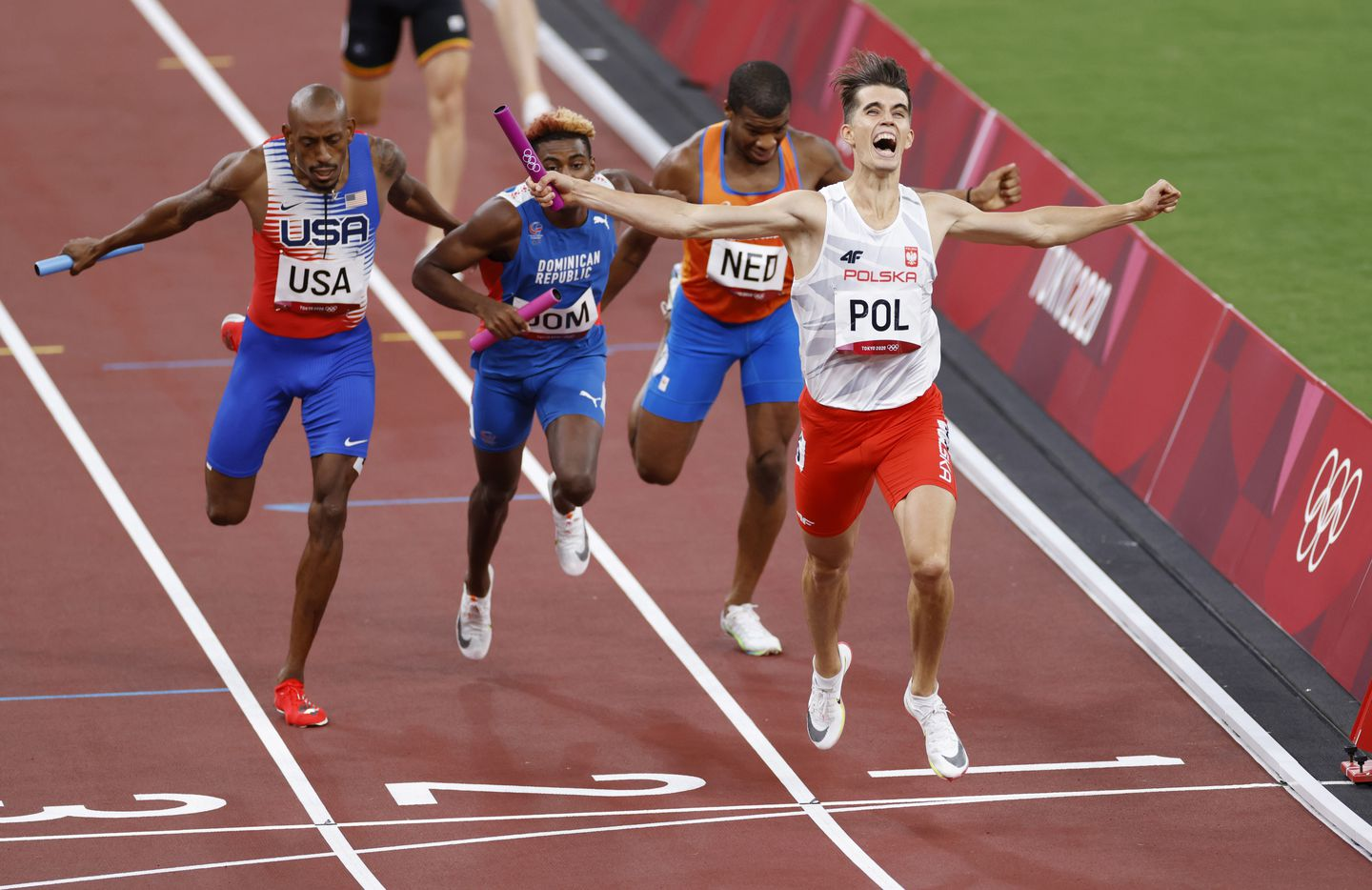 (From l to r) Poland's Kajetan Duszynski celebrates after winning and setting an Olympic record in the mixed 4x400m relay final during the postponed 2020 Tokyo Olympics at Olympic Stadium, on Saturday, July 31, 2021, in Tokyo, Japan. Poland earned a gold medal, the Dominican Republic a silver and USA took bronze. (Vernon Bryant/The Dallas Morning News)