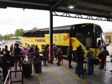 Un grupo de hispanos hace fila para abordar un autobús que se dirige a México desde Dallas.