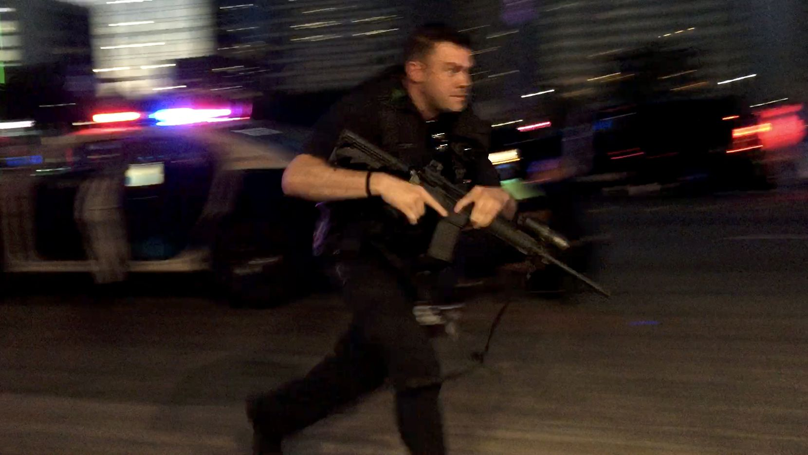 A Dallas police officer ran with a rifle as shots were fired July 7, 2016, in downtown Dallas.