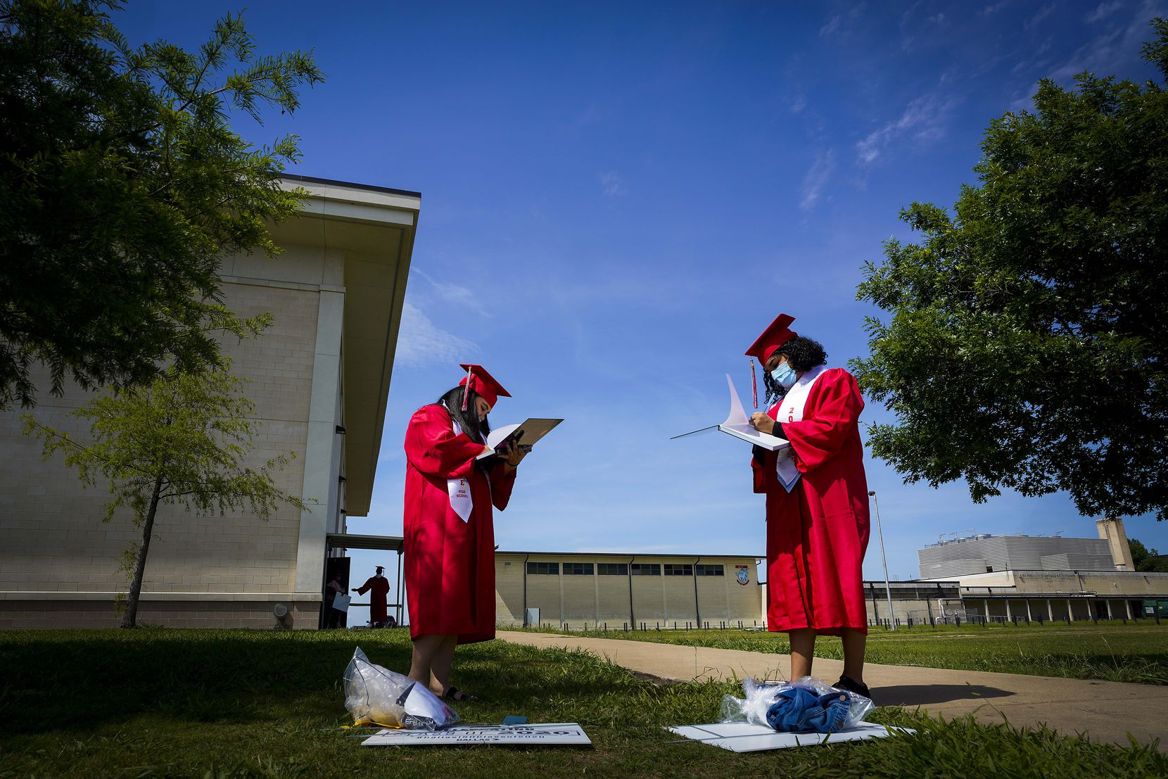 Andrea Soto (left) and Samanta Zuniga, seniors at Skyline High School, signed each other's yearbooks after picking up their graduation caps and gowns in May. Like the rest of Dallas ISD, Skyline's graduation ceremony was virtual.