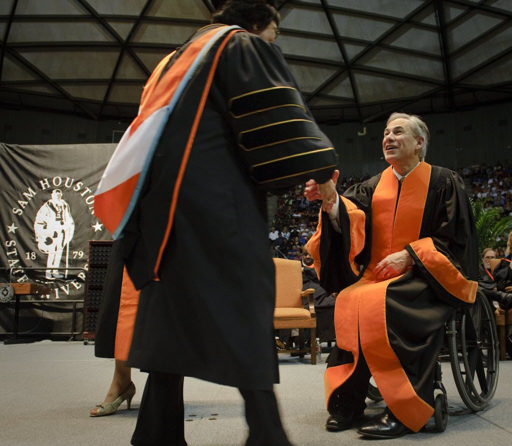 Texas Attorney General Greg Abbott, right, congratulates a doctoral graduate after delivering the commencement address at Sam Houston State University on May 15, 2010 in Huntsville, Texas.