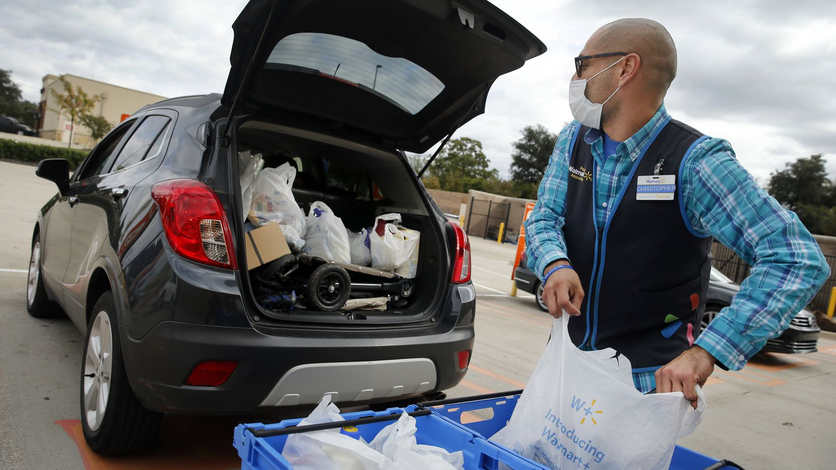 Online grocery pickup associate Christopher Juarez loads Maria Hernandez's SUV with groceries at a Walmart Supercenter in Dallas. As Dallas County sees an uptick in COVID-19 cases and related variants, some North Texas shoppers will likely turn to online grocery shopping.