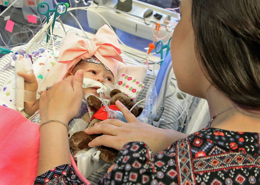 Jacqueline Solis spends a tender moment with her daughter Olivia Solis, as she recovers in intensive care at Children's Medical Center in Dallas, photographed on Tuesday, March 20, 2018. Oliva has spent her whole life thus far in cardiac ICU, has gone through two heart surgeries and 16 days of life support, and suffered a cardiac arrest and over an hour of CPR, seizures, and bleeding on the brain. She's been placed on a heart transplant list. (Louis DeLuca/The Dallas Morning News)