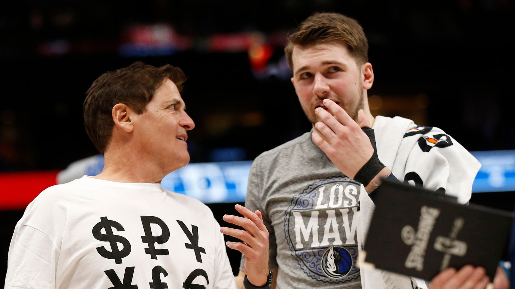 Dallas Mavericks owner Mark Cuban sports a shirt with money signs as he talks to Dallas Mavericks guard Luka Doncic (77) during the second half of play at American Airlines Center in Dallas on Friday, March 6, 2020. Dallas Mavericks defeated the Memphis Grizzlies 121-96.