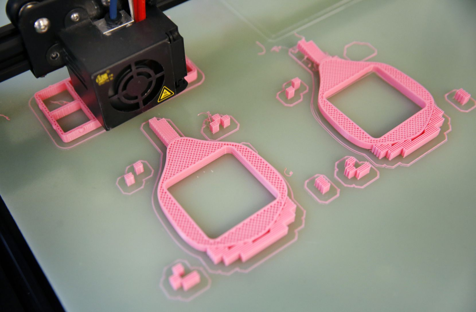 A 3-D printer creates a pink respiratory mask at Unique Software Development on N. Central Expressway in Dallas, Friday, March 27, 2020.