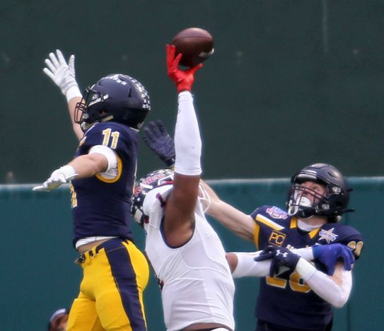 Denton Ryan receiver Ja'Tavion Sanders (1) makes a one-handed touchdown grab between the coverage of Highland Park defensive backs Garrison Vincent (11) and Ford Frazar (28) during first quarter action. The two teams played their Class 5A Division l Region ll final football playoff game at Globe Life Park in Arlington on January 1, 2021.