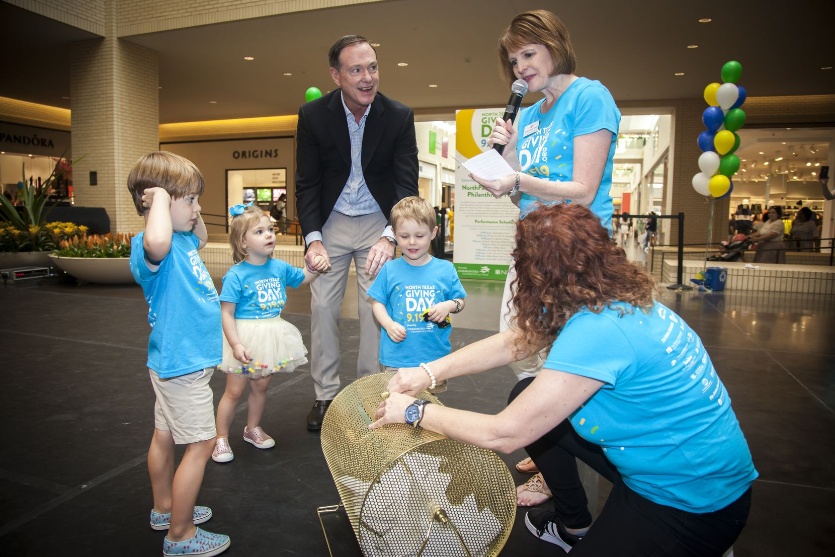Dave Scullin, president and CEO of the Communities Foundation of Texas, and his grandchildren, from left, Henry and Colette Long and Jack Scullin, helped foundation staffers Monica Egert Smith and Stephenie Barr-Hughes draw draw prize winners during North Texas Giving Day festivities at the NorthPark Family Philanthropy Festival in September 2019.         Names from left:  Dave Scullin and his grandchildren help Monica Egert Smith draw a nonprofit prizewinner's name
