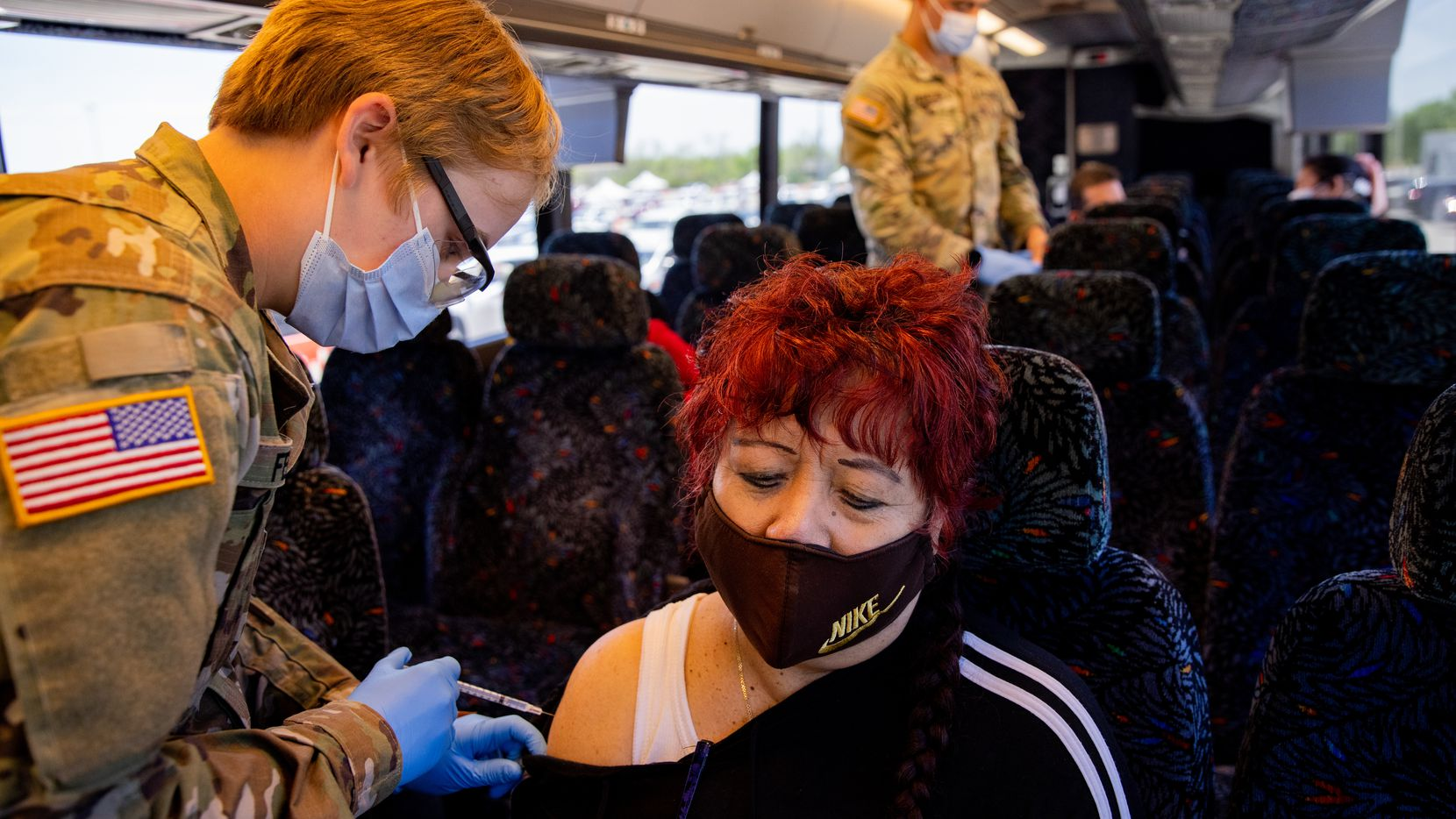 """Rosa Sanchez looks away while getting her second dose of the COVID-19 vaccine at Fair Park through the """"Registration and Transportation"""" effort by Dallas County that bused people from Bachman Recreation Center on Wednesday."""