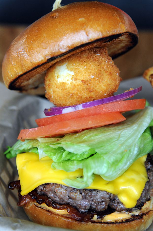 The bacon cheese burger features lettuce, tomato, onion, and is topped with a crispy fried egg at Spork in Far North Dallas, TX on March 15, 2015. (Alexandra Olivia/ Special Contributor)