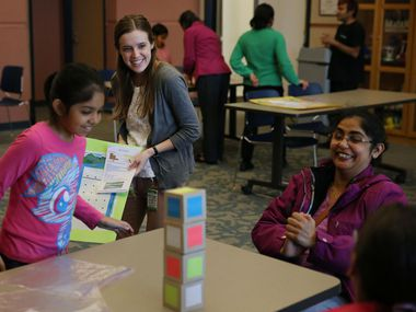 This file photo shows librarian Laura Hargrove  (center) and Aarushi Sudhakar, 9, watch as Aarushi's mother, Arati Sudhakar, solves Instant Insanity during a STEAM-based educational day at the Davis Public Library in Plano. Each of Plano's five libraries has embraced STEAM activities on-site and has kits available for checkout.