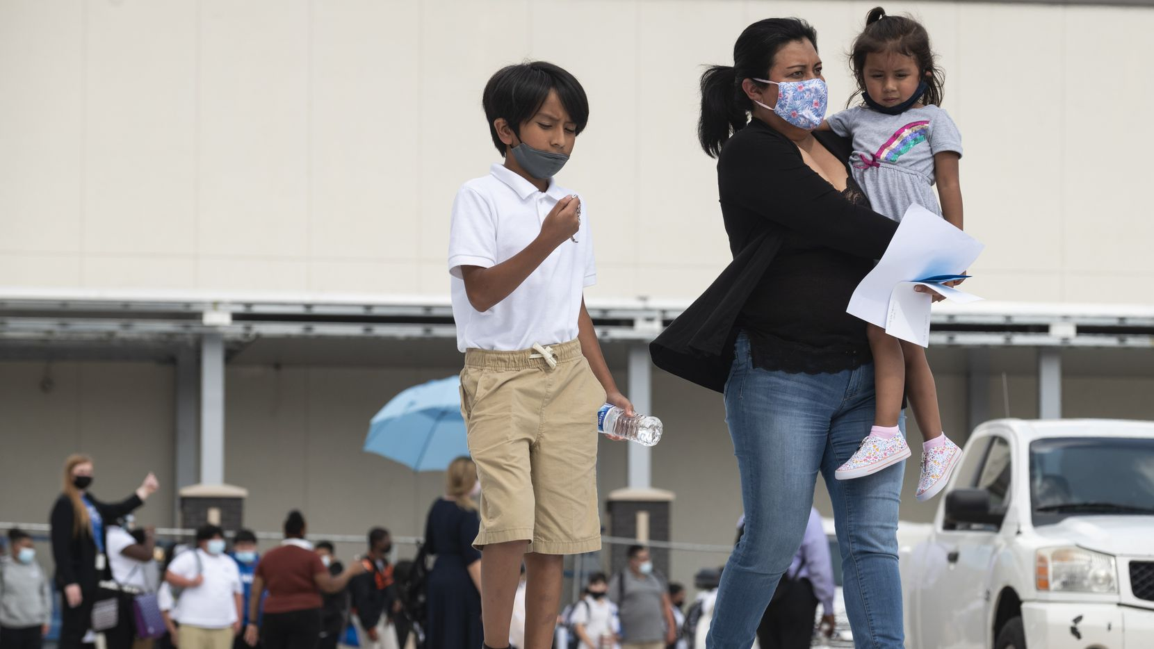 A mother walks with her children after her son's first day back to school at E.D. Walker Middle School in Dallas. Texas' under-18 population grew 6% over the past decade, but the number declined 2% in Dallas County, according to recent census data.