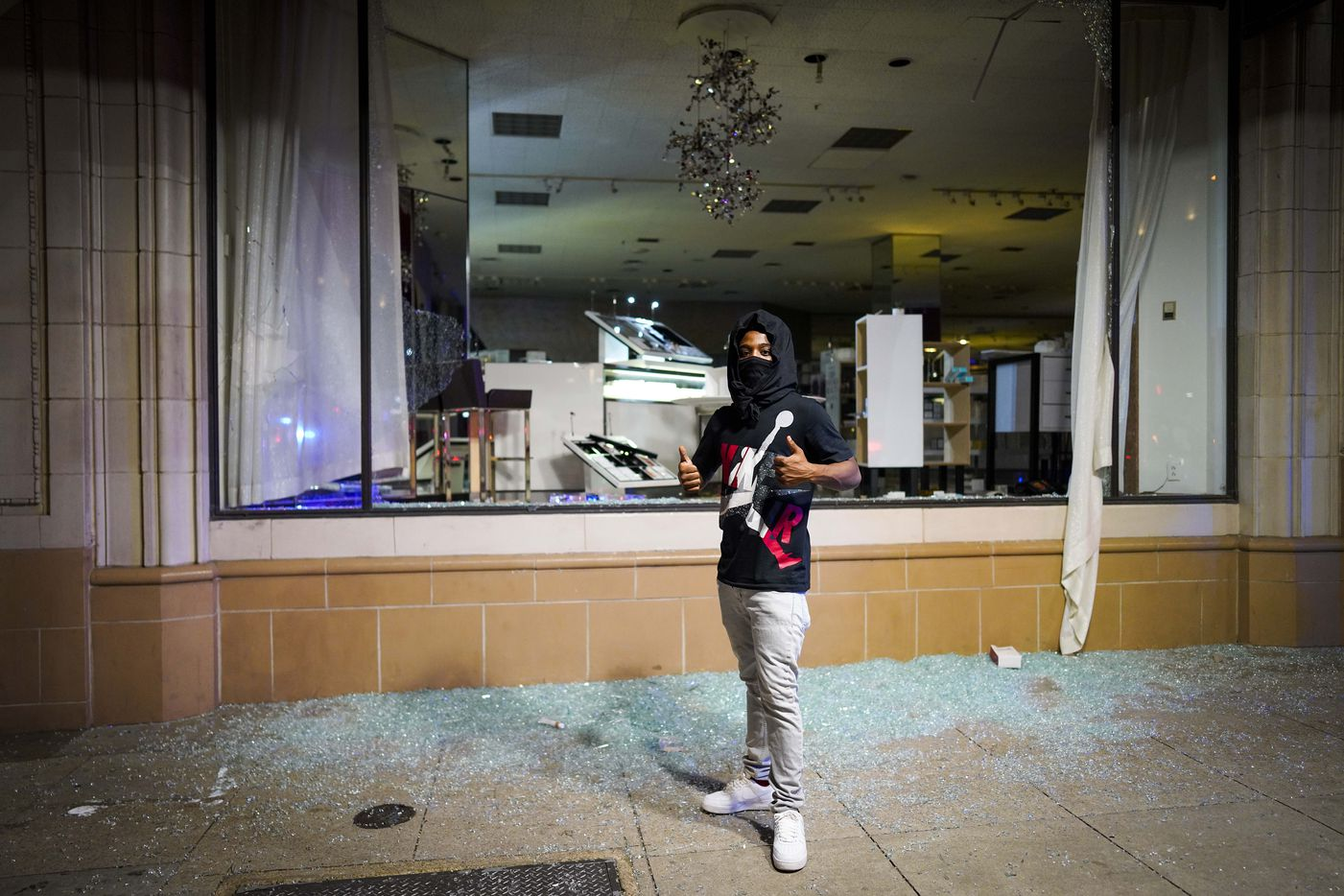 A man poses for a photo amidst broken glass after windows were smashed at the Nieman Marcus store downtown following a protest against police brutality in the early morning hours of Saturday, May 30, 2020, in Dallas. The protest against police brutality was organized by Next Generation Action Network in response to the in-custody death of George Floyd in Minneapolis.