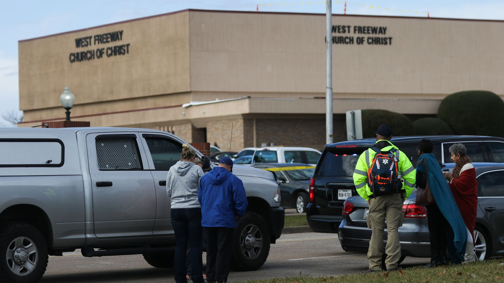 People gather outside the West Freeway Church of Christ in White Settlement on Sunday, where a gunman opened fire, killing one person and critically wounding another before churchgoers fatally shot the gunman.