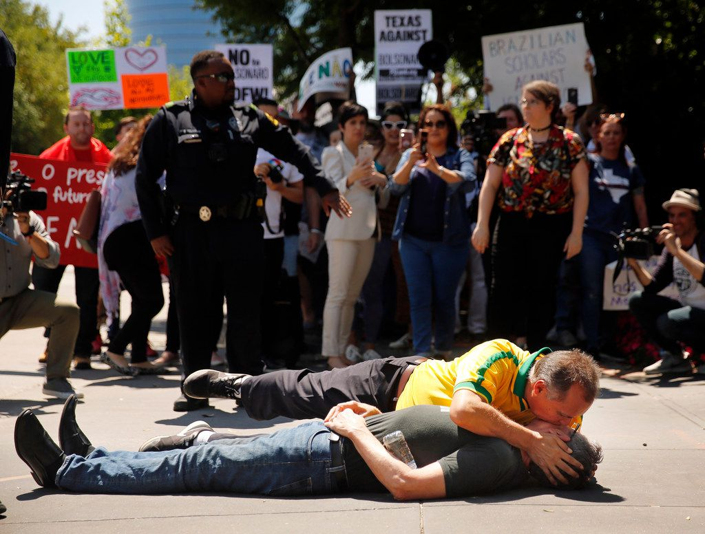 In a showing of solidarity, Romildo Ferreira (in yellow), who is a supporter of Brazilian President Jair Bolsonaro, laid down next to a protester demonstrating against Bolsonaro and embraced him outside  the Old Parkland Hospital in Dallas ahead of an event hosted by The World Affairs Council of Dallas/Fort Worth on Thursday.