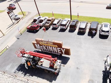 A 30-foot neon sign goes into place on top of the Chestnut Commons Parking Garage at the corner of Chestnut and Herndon streets in McKinney on Wednesday, May 7, 2020.