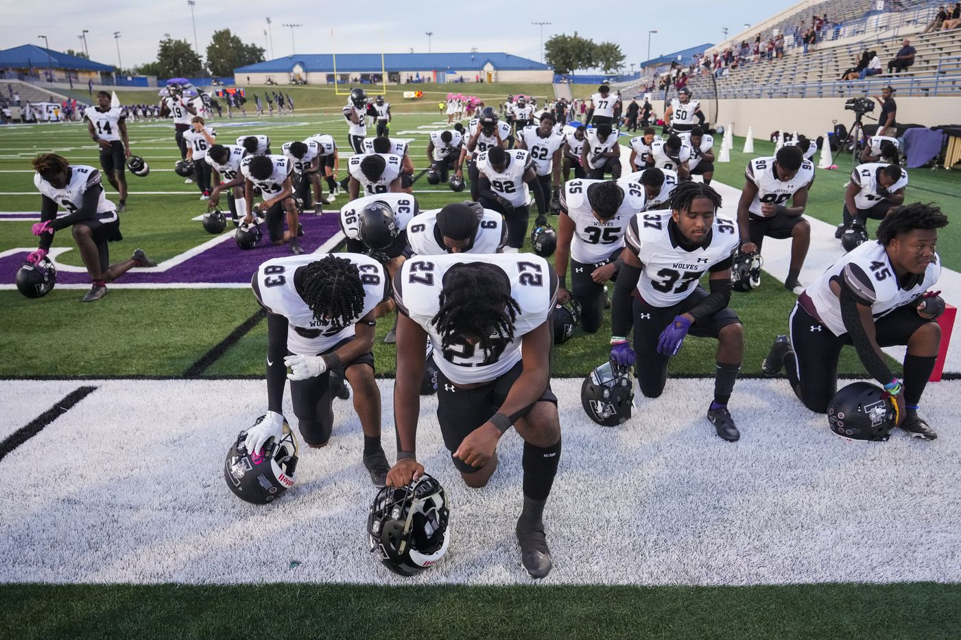 Mansfield Timberview kneel in prayer before facing Waco University in a high school football game at Waco ISD Stadium on Friday, Oct. 8, 2021, in Waco, Texas.