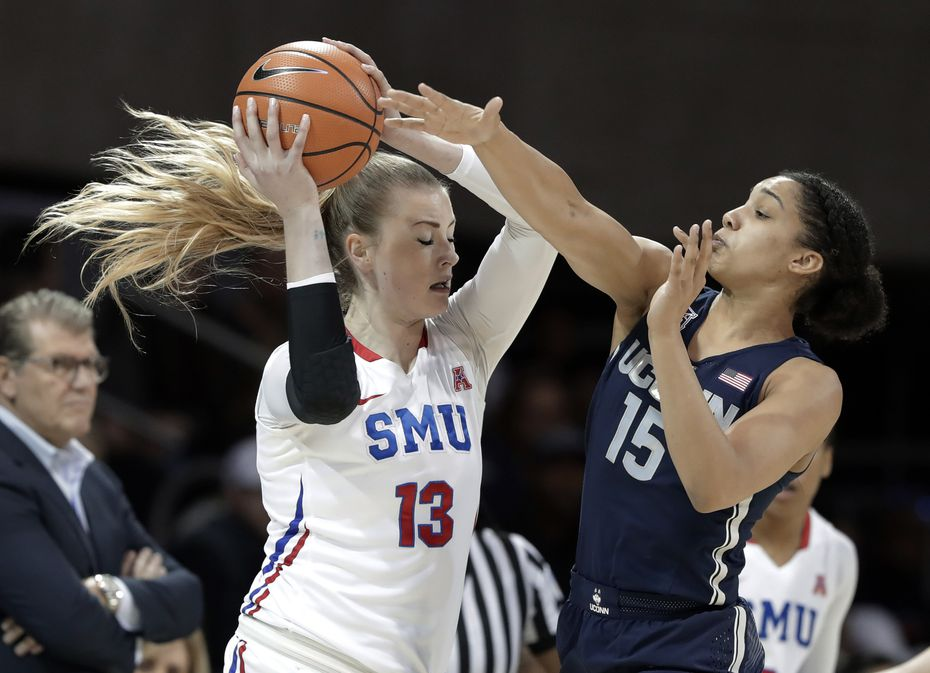 SMU's Klara Bradshaw (13) protects the ball as Connecticut forward Gabby Williams (15) attempts a steal, while UConn coach Geno Auriemma watches during the first half of an NCAA college basketball game Saturday, Feb. 24, 2018, in Dallas.