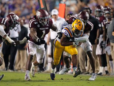 LSU running back Clyde Edwards-Helaire (22) carries against Texas A&M linebacker Buddy Johnson (1) and defensive back Keldrick Carper during the second half of an NCAA college football game in Baton Rouge, La., Saturday, Nov. 30, 2019. LSU won 50-7. (AP Photo/Gerald Herbert)