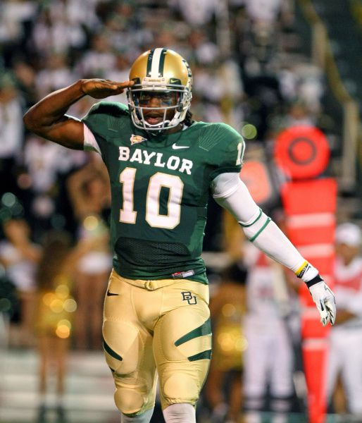 Baylor quarterback Robert Griffin III salutes after throwing a touchdown pass to wide receiver Kendall Wright in the first half of an NCAA college football game, Saturday, Oct. 8, 2011, in Waco.