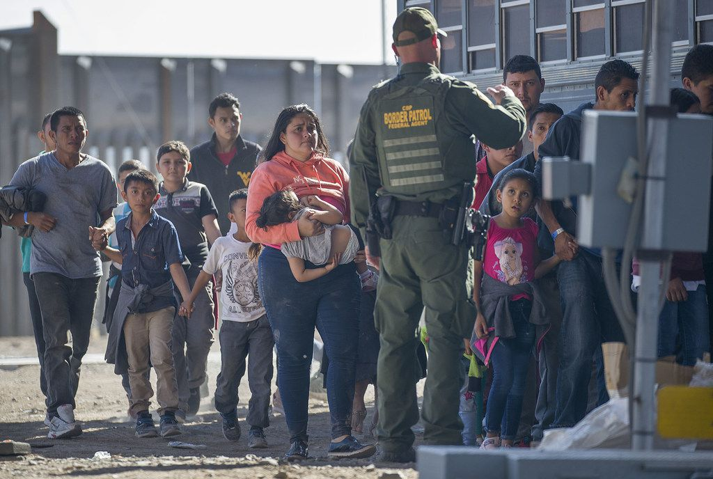 Migrants are loaded onto a bus by U.S. Border Patrol agents after being detained when they crossed  into the United States from Mexico on June 01 in El Paso.