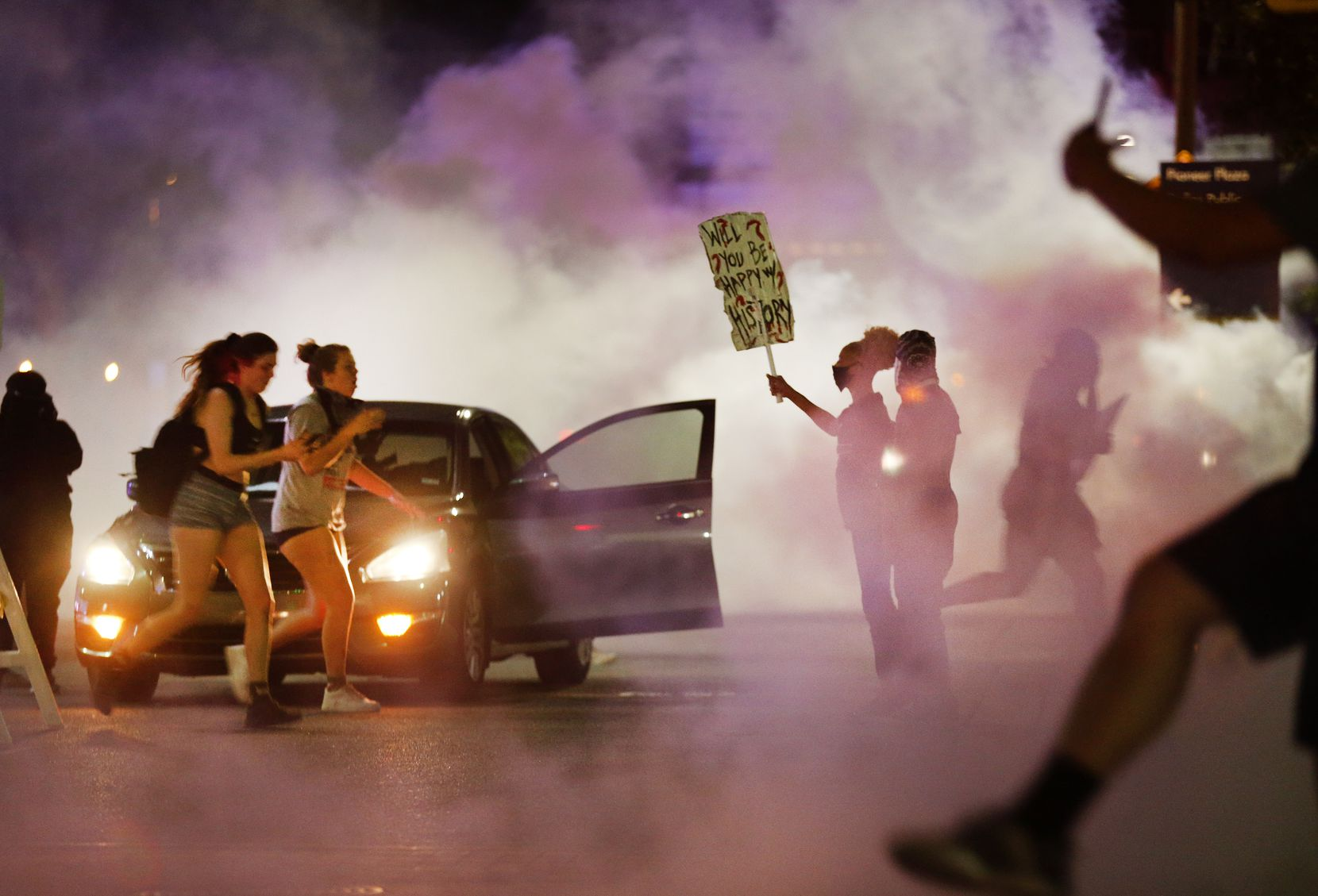 A pair of protestors are overcome with tear gas as they run from Dallas Police tactical officers at Young St. and S. Griffin St. in downtown Dallas, Friday, May 29 2020. People were marching in protest of the in-custody death of George Floyd when they confronted Dallas Police tactical officers and tear gas was fired.
