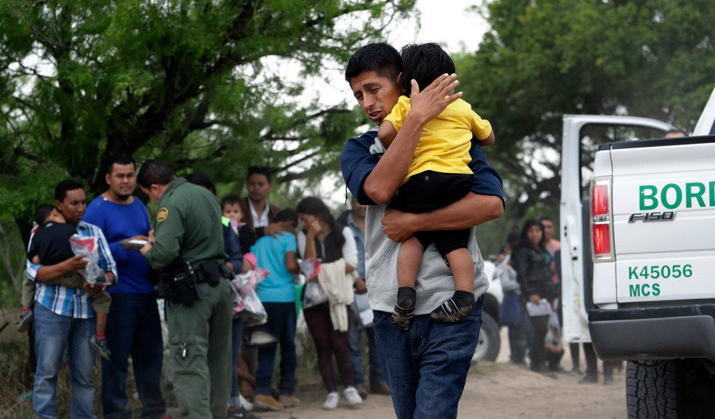 Jose Fermin Gonzalez Cruz holds his son, William Josue Gonzales Garcia, 2, on March 14 as they wait with other families who crossed the nearby U.S.-Mexico border near McAllen, Texas, for Border Patrol agents to check names and documents. Immigration authorities say they expect the ongoing surge of Central American families crossing the border to multiply in the coming months.